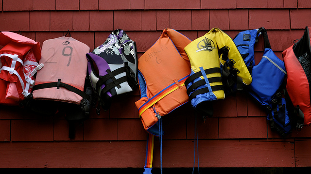Personal Flotation Devices and life jackets against a wall